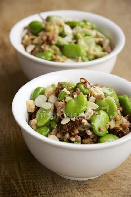 Grano saraceno e insalata di fave con nocciole e pomodori in ciotola di legno — Foto stock
