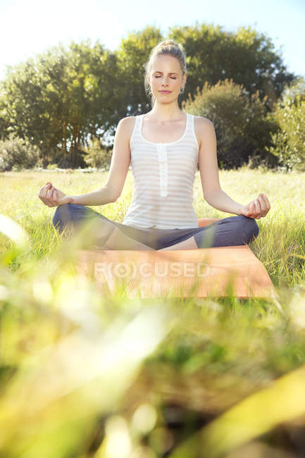 Woman practising yoga in a meadow — Stock Photo