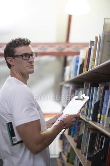 Молодой кавказский студент ищет книги в библиотеке — стоковое фото