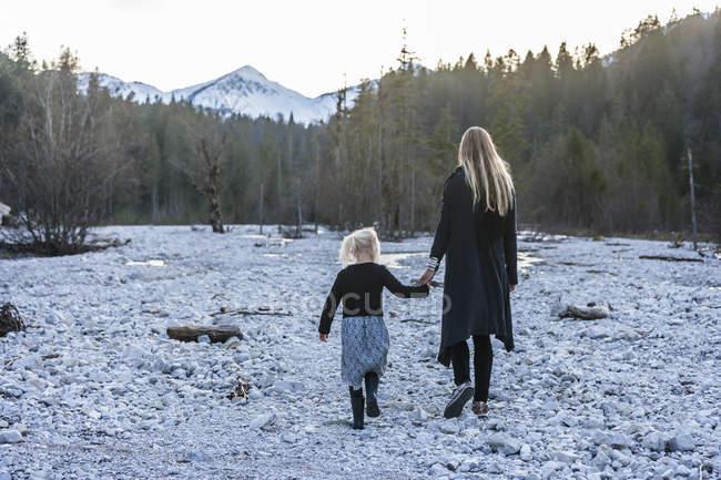 Alemania, Baviera, Lindergriess, madre e hija caminando en lecho seco del arroyo - foto de stock