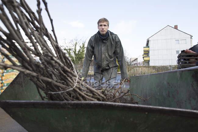 Молодий садівник на роботі, несучи чагарник — стокове фото