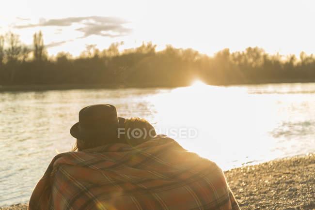 Пара, наслаждающаяся закатом, завернутая в одеяло на берегу реки — стоковое фото