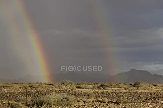 Arco iris brillante de África, Namibia, en Sossusvlei, montañas en el fondo - foto de stock