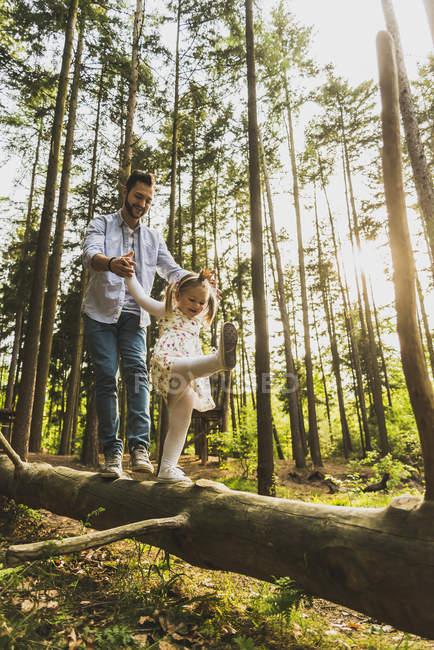 Vater helfen Mädchen balancing auf Baumstamm — Stockfoto