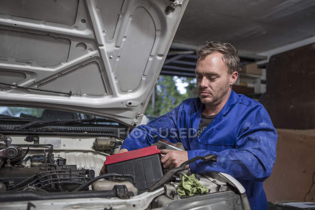 Man working on car in home garage removing battery — Stock Photo