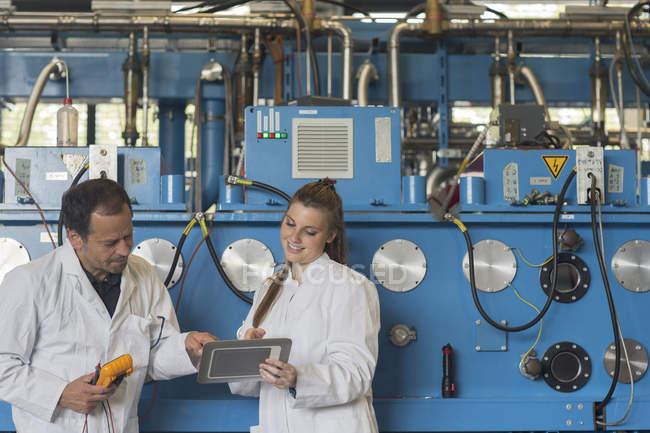 Deux techniciens contrôlent les machines en usine — Photo de stock