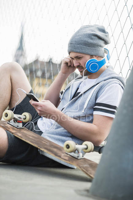 Young man with skateboard listening music from smartphone — Stock Photo