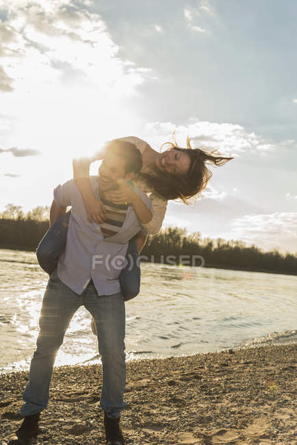 Happy young couple having fun at the riverside — Stock Photo