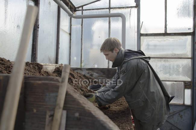 Молодий садівник на роботі, заповнення грунту матері — стокове фото