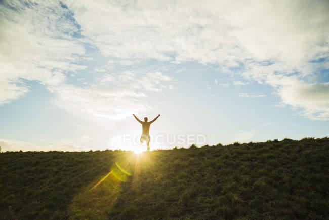 Cheering young man looking at rising sun — Stock Photo