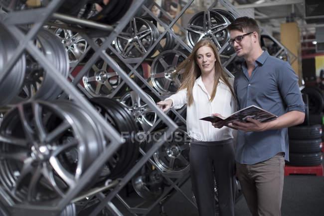 Uomo e donna al negozio di pneumatici fare una selezione per una vendita — Foto stock
