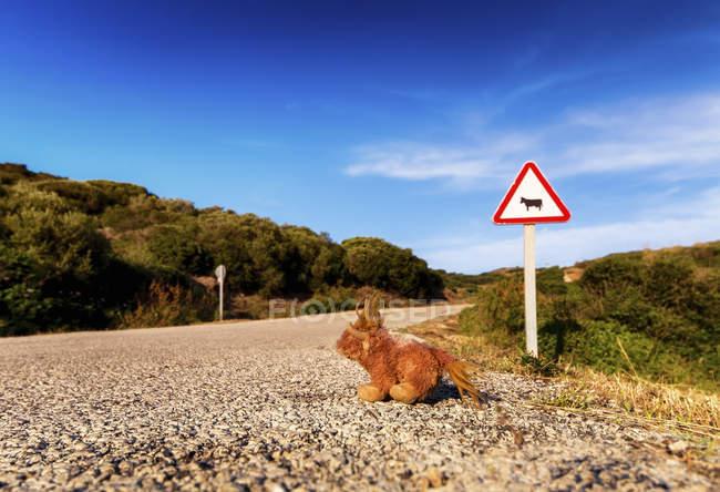 Espanha, Ilhas Baleares, Menorca, Sinal de estrada em estrada com brinquedo macio — Fotografia de Stock