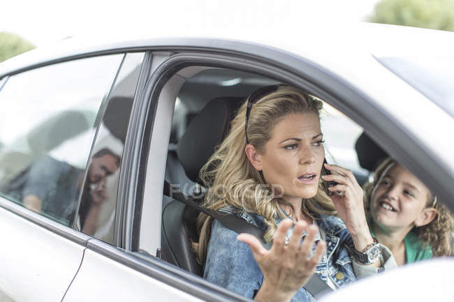 Frustrated woman in car with child stuck in traffic jam — Stock Photo