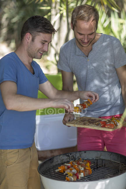 Happy gay couple preparing food on barbecue grill — Stock Photo