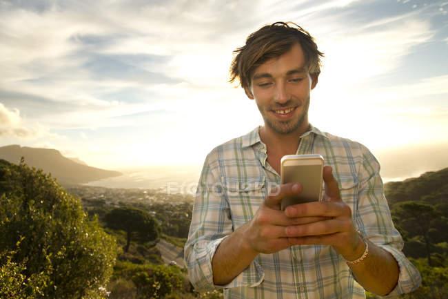 Молодий чоловік на узбережжі, за допомогою мобільного телефону — стокове фото