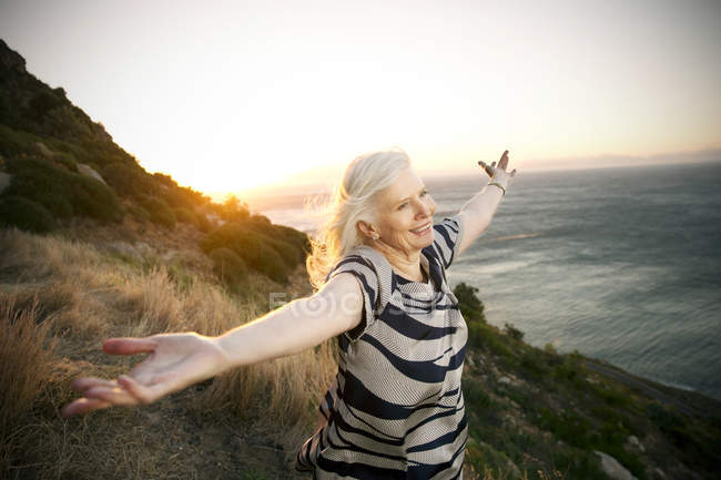 Portrait of happy senior woman with outstretched arms — Stock Photo