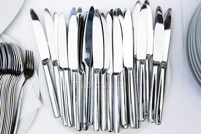 Cuchillos de plata en la mesa con tela blanca - foto de stock