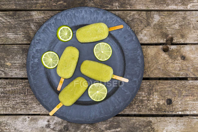 Plate of avocado ice lollies and slices of lime — Stock Photo
