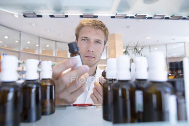 Young pharmacist choosing medicine bottles — Stock Photo