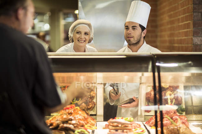 Male chef and assistant helping clients at food display — Stock Photo