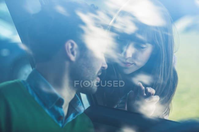 Paar verabschiedet sich durch Windschutzscheibe — Stockfoto