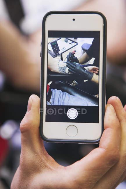 Männliche Hand, die Smartphone mit Fotografie der Tattoo-Künstler bei der Arbeit — Stockfoto