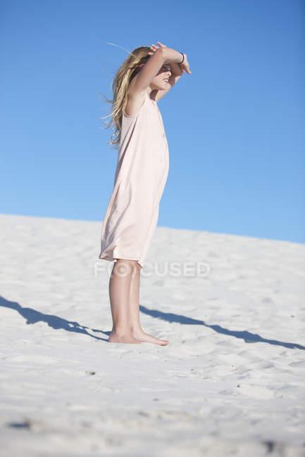 Девочка стоит на пляже, глядя вдаль — стоковое фото