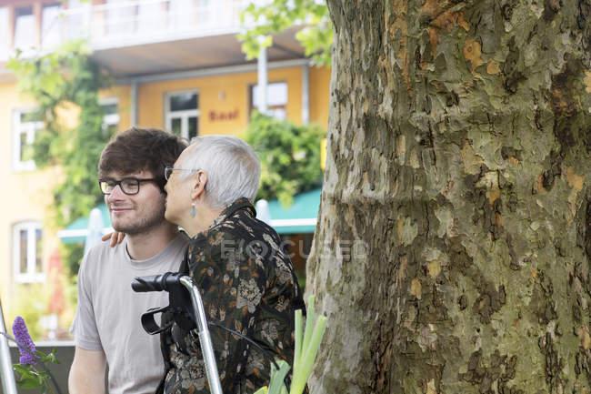 Старший жінка, підтримуючи молодої людини на дерево — стокове фото