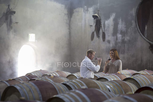 Man and woman tasting wine in cellar — Stock Photo