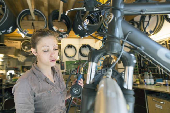 Молода жінка в велосипед магазин ремонту inflating шини — стокове фото