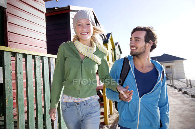 Young couple hand in hand at beach hut — Stock Photo