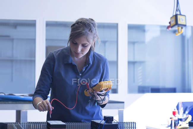 Technician in workshop checking electrical device — Stock Photo