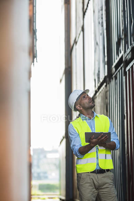 Man with digital tablet wearing reflective vest at container port — Stock Photo