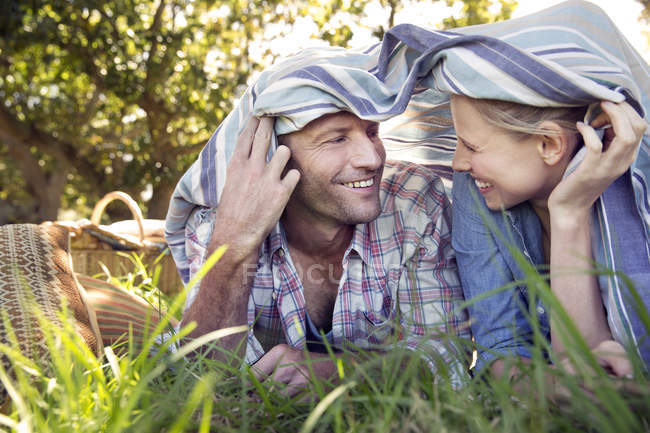 Happy couple lying on meadow under a blanket — Stock Photo