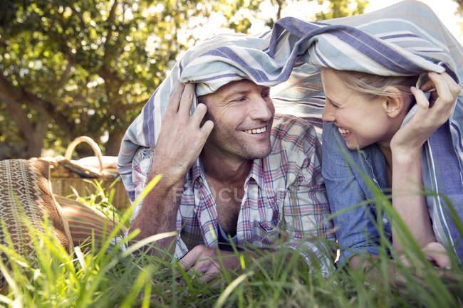 Deitado no pasto, debaixo de um cobertor de casal feliz — Fotografia de Stock