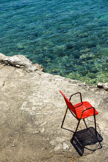 Croatia, Dubrovnik, red chair standing at seafront — Stock Photo