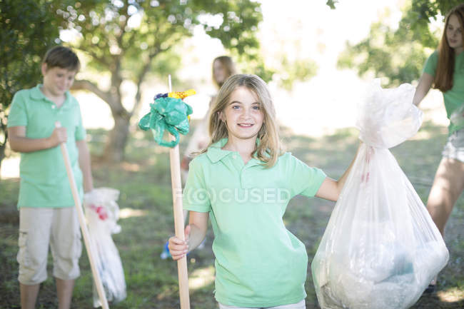 Children picking up garbage in a park — Stock Photo