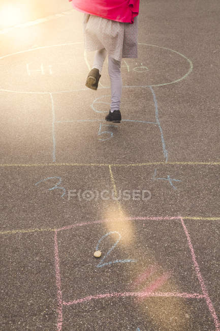 Little girl playing hopscotch outdoors — Stock Photo
