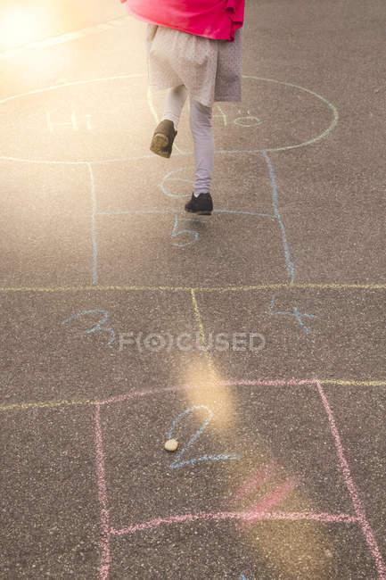 Fillette jouant à la marelle en plein air — Photo de stock