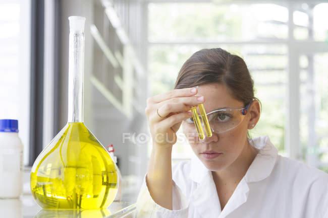 Портрет молода жінка хімік тримає скляні трубочки з жовтими реагенту — стокове фото