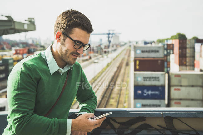 Man at freight yard looking at cell phone — Stock Photo