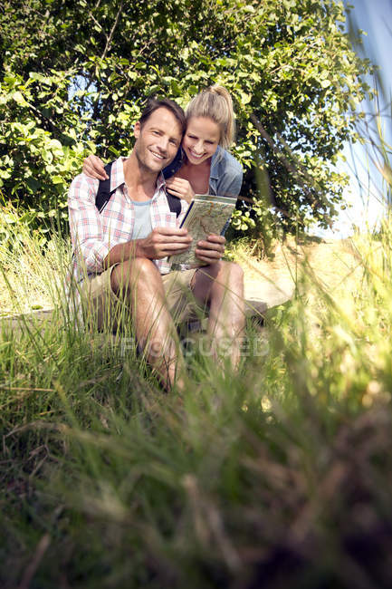 Happy hiking couple with map taking a break — Stock Photo