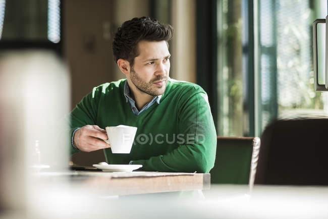 Людина п'ють кави в кафе і дивитися вбік — стокове фото