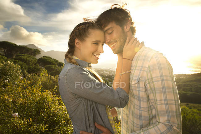 Tender young couple at the coast at sunset — Stock Photo