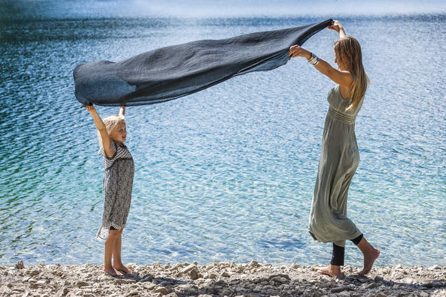 Austria, Tyrol, Lake Plansee, mother and daughter holding cloth at lakeshore — Stock Photo