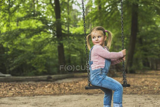 Посміхається дівчина сидить на гойдалках — стокове фото