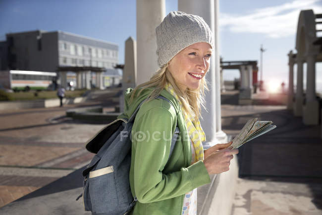 Tourist with backpack holding map — Stock Photo