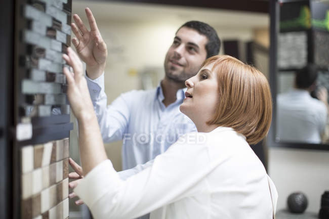 Bathroom shop salesman showing tile samples to female customer — Stock Photo