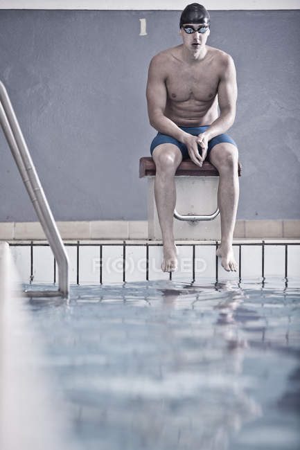 Кавказский пловец в закрытом бассейне сидит на стартовом блоке — стоковое фото