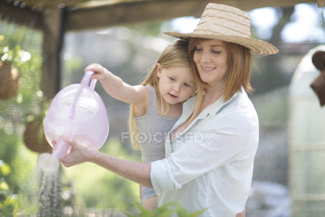 Portrait of woman and little daughter watering plants with watering can — Stock Photo
